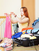 Girl choosing clothes for vacation — Stock Photo
