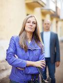 Man walks behind woman on street — 图库照片