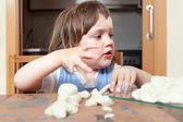 Cute girl sculpts dough toys — Stock Photo