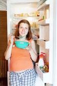 Pregnant woman eats from fridge — Stock Photo