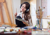 Woman in headphones paints on canvas — Stock Photo