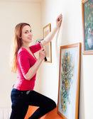 Mulher de pendurar os quadros de arte — Fotografia Stock