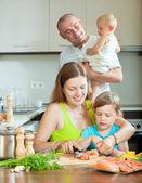 Genitori con bambini, cucinare il pesce — Foto Stock