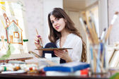 Yuong artist paints the house — Stock Photo