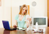 Serious blonde woman reading about medications — Stock Photo