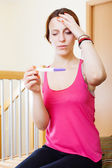 Sad serious woman with pregnancy test — Stock Photo