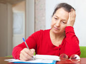 Sad mature woman with utility bills — Stock Photo