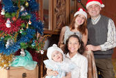 Family with child in christmas hats — Stock Photo