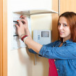 Red-haired cute woman turning off the light-switch at power cont — Stock Photo