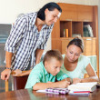 Schoolboy and parents together doing homework   — Stock Photo