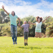 family  with teenage boy jumping in  park — Stock fotografie