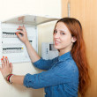 Long-haired woman turning off the light-switch at power control — Stock Photo