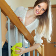 Stock Photo: Cheerful womcleaning stair railings