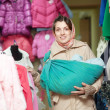 Woman with baby in ringsling chooses clothes  — ストック写真