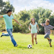 Family with teenager playing in soccer — Stock Photo