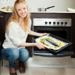 Cheeful woman cooking fish in oven  — Stock Photo