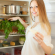 Long-haired woman near opened refrigerator   — Stock Photo