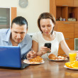 Happy couple using electronic devices during breakfast — Photo #35139769