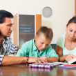 Schoolboy doing homework with parents — Stock Photo
