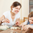 Stock Photo: Young womand her child sculpting from clay or dough in home