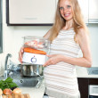 Happy pregnant woman cooking — Stockfoto