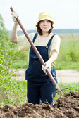 Woman scatters manure in field — Stock Photo