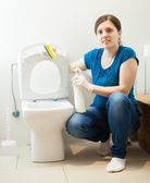 Woman cleaning toilet with sponge and cleaner — Stock Photo