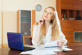 Pensive woman reading documents at home — Stock Photo
