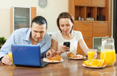 Happy couple using electronic devices during breakfast — Stock Photo
