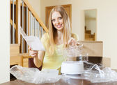 Cheerful woman unpacking new electric steamer at home — Stock Photo