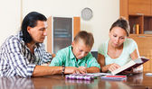 Schoolboy doing homework with parents — Stockfoto