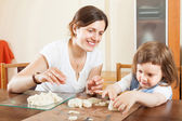Young woman and her child sculpting from clay or dough in home — Stock Photo