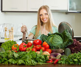 Happy woman cooking with heap of raw vegetables — Stock Photo