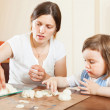 Foto Stock: Girl with her mother learns to mold dough figurines