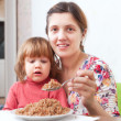 Woman with child eats buckwheat   — Stock Photo