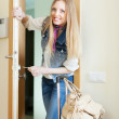 Happy woman loocking door and leaving her home — Stock Photo #35140327