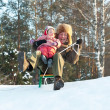 Happy man with child sliding on sleds   — Stock Photo
