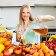 Positive blonde long-haired girl making fresh beverages — Stock Photo