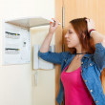 Sad woman turning off the light-switch — Stock Photo