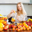 Smiling woman making fruits beverages  — Stock Photo