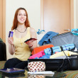 Woman sitting on sofa and packing suitcase — Stok fotoğraf