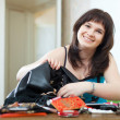 positive woman can not finding anything in  handbag   — Stock Photo