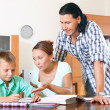 Parents with schoolboy doing homework — Stockfoto