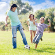 Family with teenager child playing with soccer ball — Stock Photo
