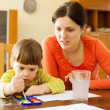 Young woman and  child painting on paper   — Stock Photo