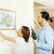 Middle-aged  couple hanging the art picture — Stock Photo