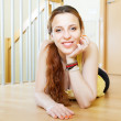 Happy girl lying on hardwood floor   — Stock Photo