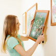 Smiling blonde woman hanging  picture   — Stock Photo