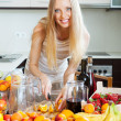 Cheerful housewife making cocktail with fruits — Stock Photo #35141351