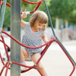 Stock Photo: Girl in dress climbing on ropes
